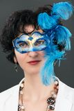 Woman with blue eyes wearing a feathered Venetian mask Stock Photography