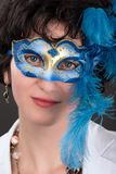 Woman with blue eyes wearing a feathered Venetian mask Royalty Free Stock Images
