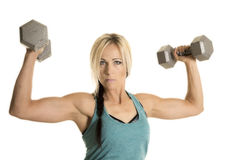 Woman in blue fitness tank top hold up weights looking Royalty Free Stock Photos