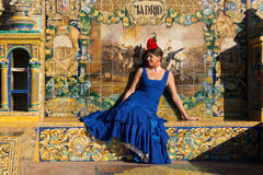 The woman with blue flamenco dress sitting in Plaza de Espana Stock Photography