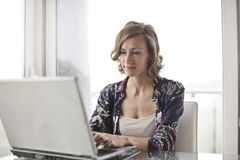 Woman in Blue Floral Top Sitting While Using Laptop Royalty Free Stock Photo