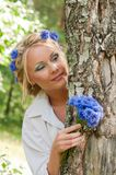 Woman with blue flowers peeking from behind a tree Stock Photos