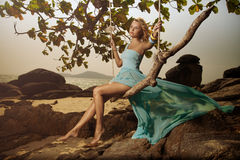 Woman In Blue Fluttering Dress Swinging On A Beach Swi stock photography