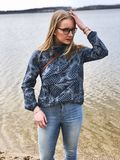 Woman in Blue and Gray Long-sleeved Shirt and Blue Denim Jeans Near Body of Water Stock Images