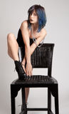 Woman With Blue Hair and Black Lipstick Leaning Over Chair. An image of a woman wearing a bodysuit and combat boots leaning on a black chair Royalty Free Stock Photo