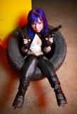 Woman with blue haircut in leather wear holding two guns sirs in the tire Royalty Free Stock Images