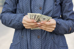 Woman in blue jacket counting money Royalty Free Stock Image