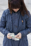 Woman in blue jacket counting money Royalty Free Stock Images