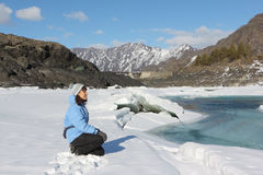 The woman in a blue jacket looking at the thawing river Royalty Free Stock Image