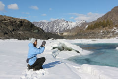 The woman in a blue jacket photographing the thawing river Royalty Free Stock Image