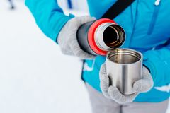 Woman in blue jacket pouring hot tea from a thermos Royalty Free Stock Photos