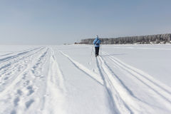 The woman in a blue jacket skiing on the snow Stock Photos