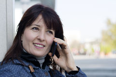 Woman in blue jacket using her phone Stock Photo