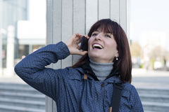 Woman in blue jacket using her phone Royalty Free Stock Photography