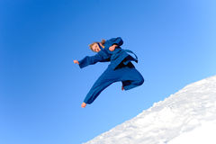 Woman in blue kimono. Young woman in blue kimono do exercise on snow Royalty Free Stock Image