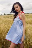 Woman in a blue light dress stands in a field Royalty Free Stock Photos