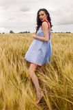 Woman in a blue light dress stands in a field Royalty Free Stock Image