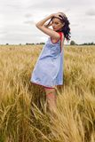Woman in a blue light dress stands in a field Stock Photos