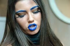 Woman with blue lipstick and unique makeup. Woman with blue lipstick and eyebrows, unique makeup with feather eyelashes. Long brunette hair and smooth skin stock photos