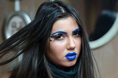 Woman with blue lipstick and unique makeup. Woman with blue lipstick and eyebrows, unique makeup with feather eyelashes. Long brunette hair and smooth skin royalty free stock photography