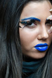 Woman with blue lipstick and unique makeup. Woman with blue lipstick and eyebrows, unique makeup with feather eyelashes. Long brunette hair and smooth skin stock images