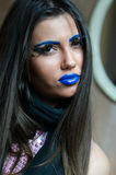 Woman with blue lipstick and unique makeup. Woman with blue lipstick and eyebrows, unique makeup with feather eyelashes. Long brunette hair and smooth skin royalty free stock image