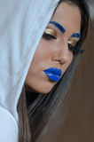 Woman with blue lipstick and unique makeup. Woman with blue lipstick and eyebrows, unique makeup with feather eyelashes wearing and covers her hair with a white royalty free stock photos