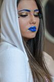 Woman with blue lipstick and unique makeup. Woman with blue lipstick and eyebrows, unique makeup with feather eyelashes wearing and covers her hair with a white royalty free stock images