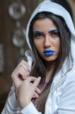 Woman with blue lipstick and unique makeup. Woman with blue lipstick and eyebrows, unique makeup with feather eyelashes wearing and covers her hair with a white royalty free stock photo