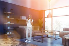Woman in blue living room with sofas. Smiling woman with coffee standing in blue living room interior with wooden floor, beige sofas, wooden coffee tables and royalty free stock photos
