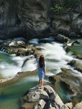 Woman in Blue Long-sleeved Dress Standing in Middle of Rock With Raging Water Royalty Free Stock Photo