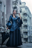 Woman in blue near old building. Woman dressed in blue victorian dress stand near old building Stock Image