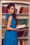 Woman in blue open back dress with lace reading book.  Romantic Stock Photos
