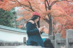 Woman in Blue Parka Jacket Sitting on Grey Concrete Bench Reading Book Stock Images