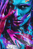 Woman in blue and pink paint with hand on face Royalty Free Stock Photo