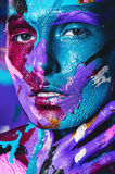 Woman in blue and pink paint with hand near face Royalty Free Stock Image