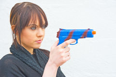 Woman with blue pistol. An image of an attractive model holding a replica gun, infact of child's plastic toy pistol Stock Images