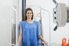 Woman In Blue Protective Clothing Undergoing Chest X-ray Scan. Portrait of mid adult woman in blue protective clothing undergoing chest X-ray scan at hospital stock photos