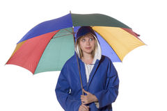 Woman in blue rain coat looking pessimistic. Young woman in a blue rain coat is looking pessimistic upwards Royalty Free Stock Photo