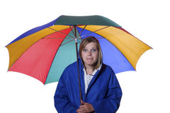 Woman in blue rain coat looking pessimistic. Young woman in a blue rain coat is looking pessimistic upwards Royalty Free Stock Images
