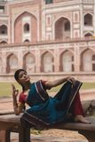 Woman in Blue, Red, and Purple Saree Dress Lying on Bench royalty free stock image