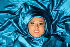 Woman with blue satin Royalty Free Stock Image