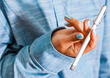 Woman in blue shirt Hold pen in your hand. pen spinning Royalty Free Stock Images