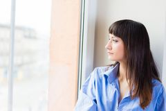 Woman in a blue shirt looking out the window Stock Photos