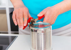 Woman in blue shirt opening a can in the kitchen Stock Photo