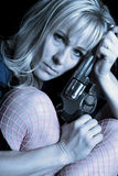 Woman blue shirt and pink fishnets hold gun against head close Stock Photo