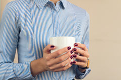 Woman in a blue shirt and red manicure holding a white cup with Royalty Free Stock Photos
