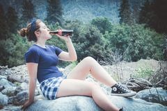 Woman In Blue Shirt Sitting On Rock Drinking Coca-cola stock images