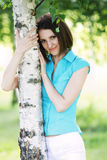 Woman in blue shirt at tree Stock Images