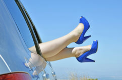 Woman with blue shoes by the way the car window on Stock Images